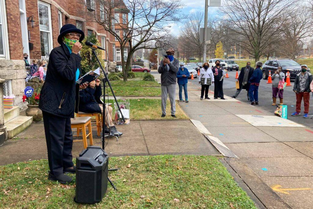 Ms. Barbara speaking to crowd of people on the sidewalk