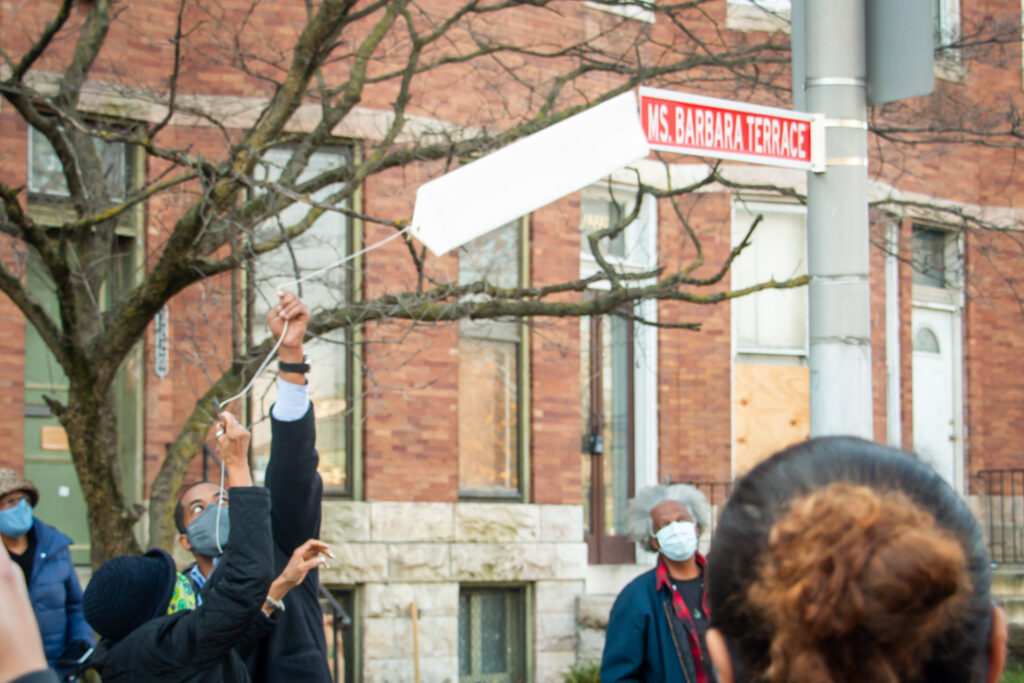 """Ms. Barbara and Nick Mosby unwrapping the """"Ms. Barbara Terrace"""" ceremonial street sign"""